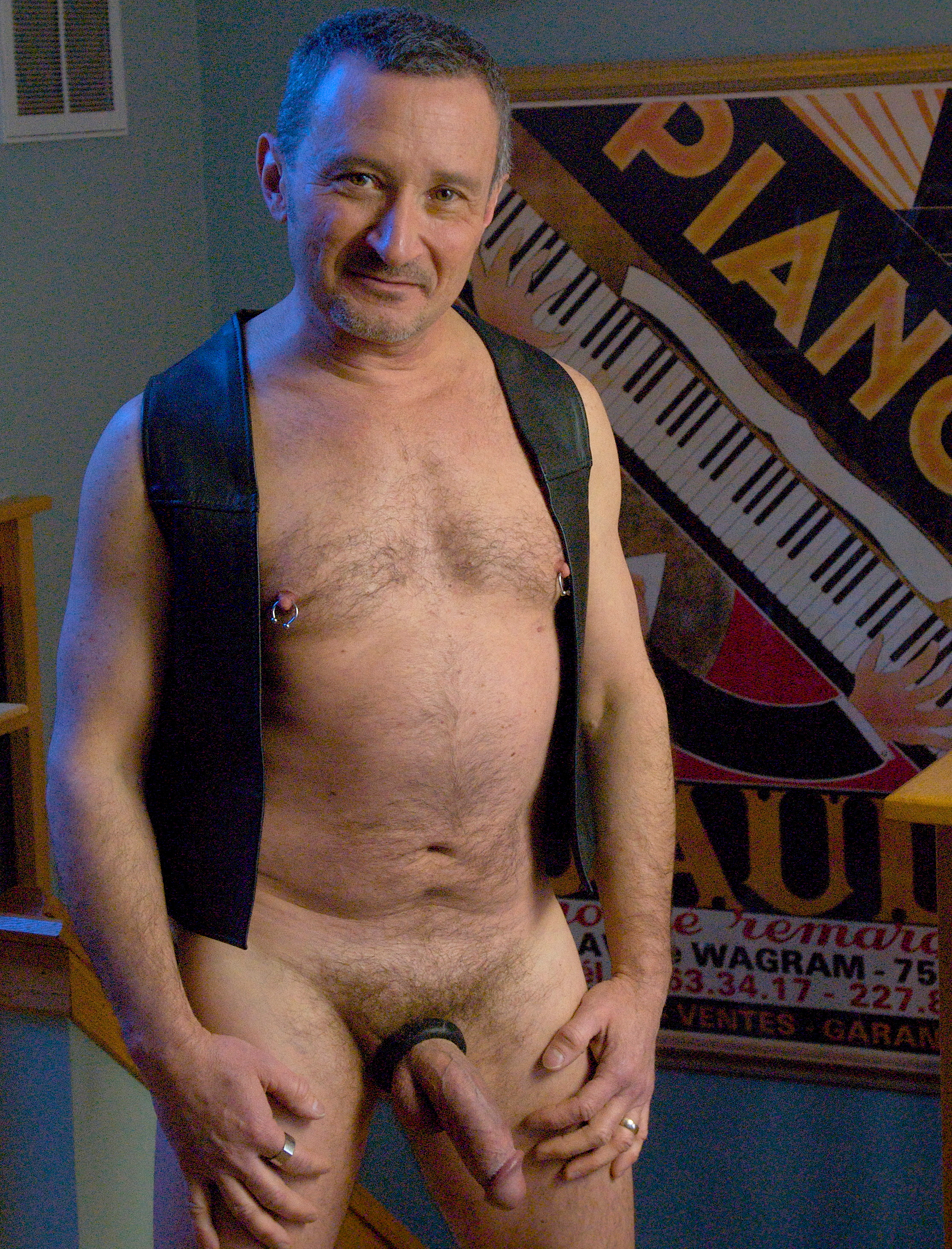 Nude man in leather vest with cock ring