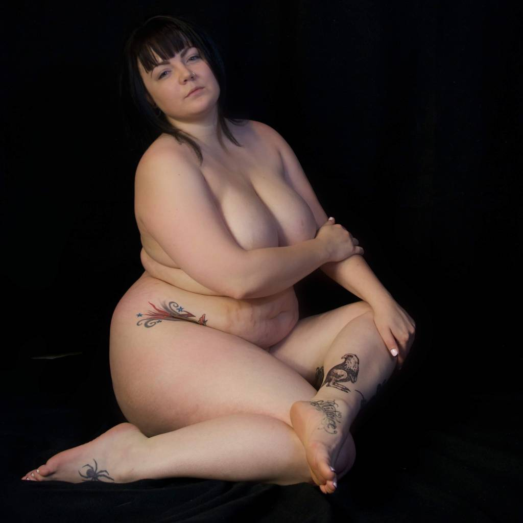 Nude full-figured woman seated