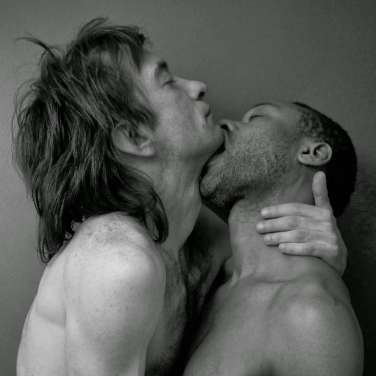 Gay men embrace and kiss
