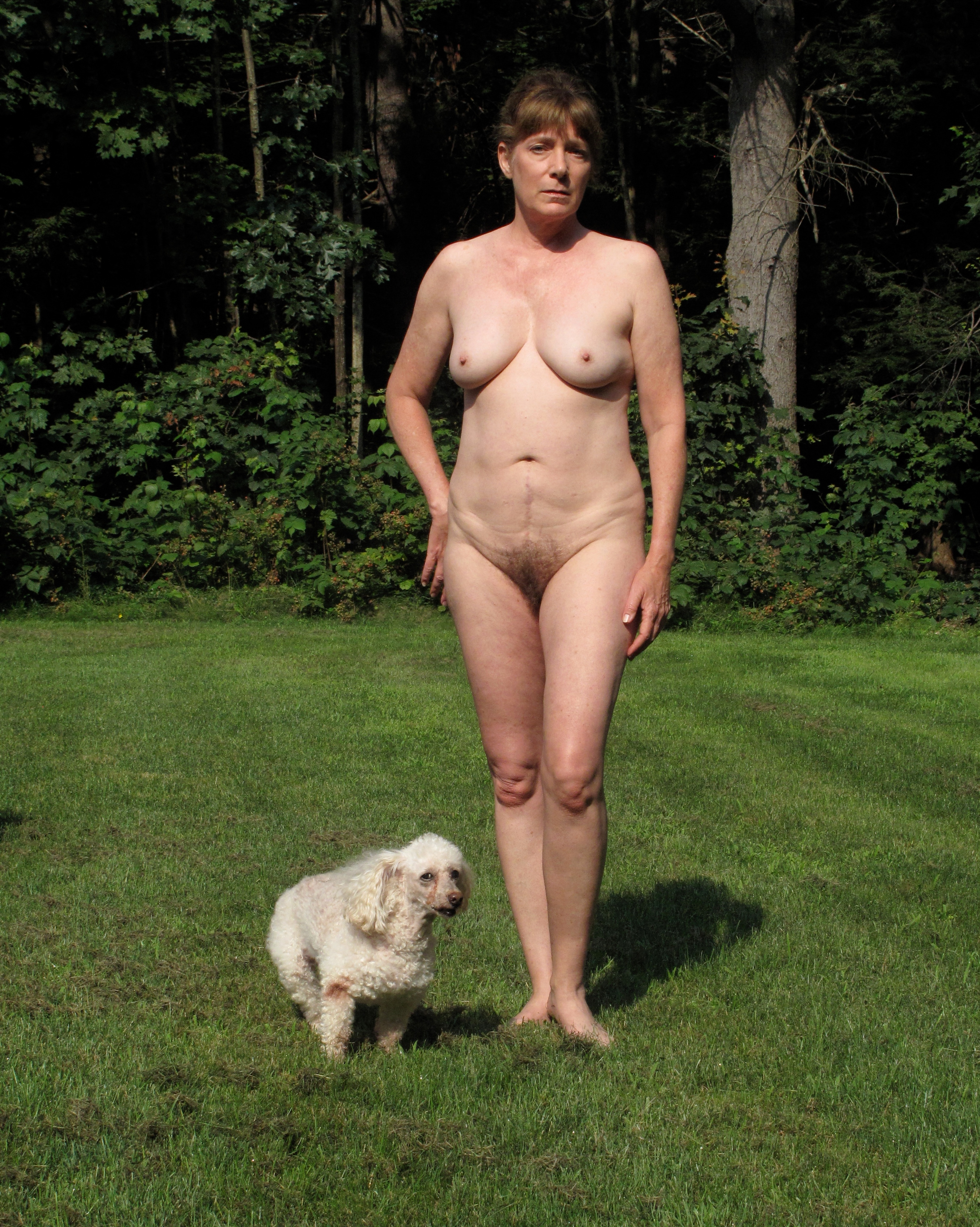 Naked woman in her backyard with dog
