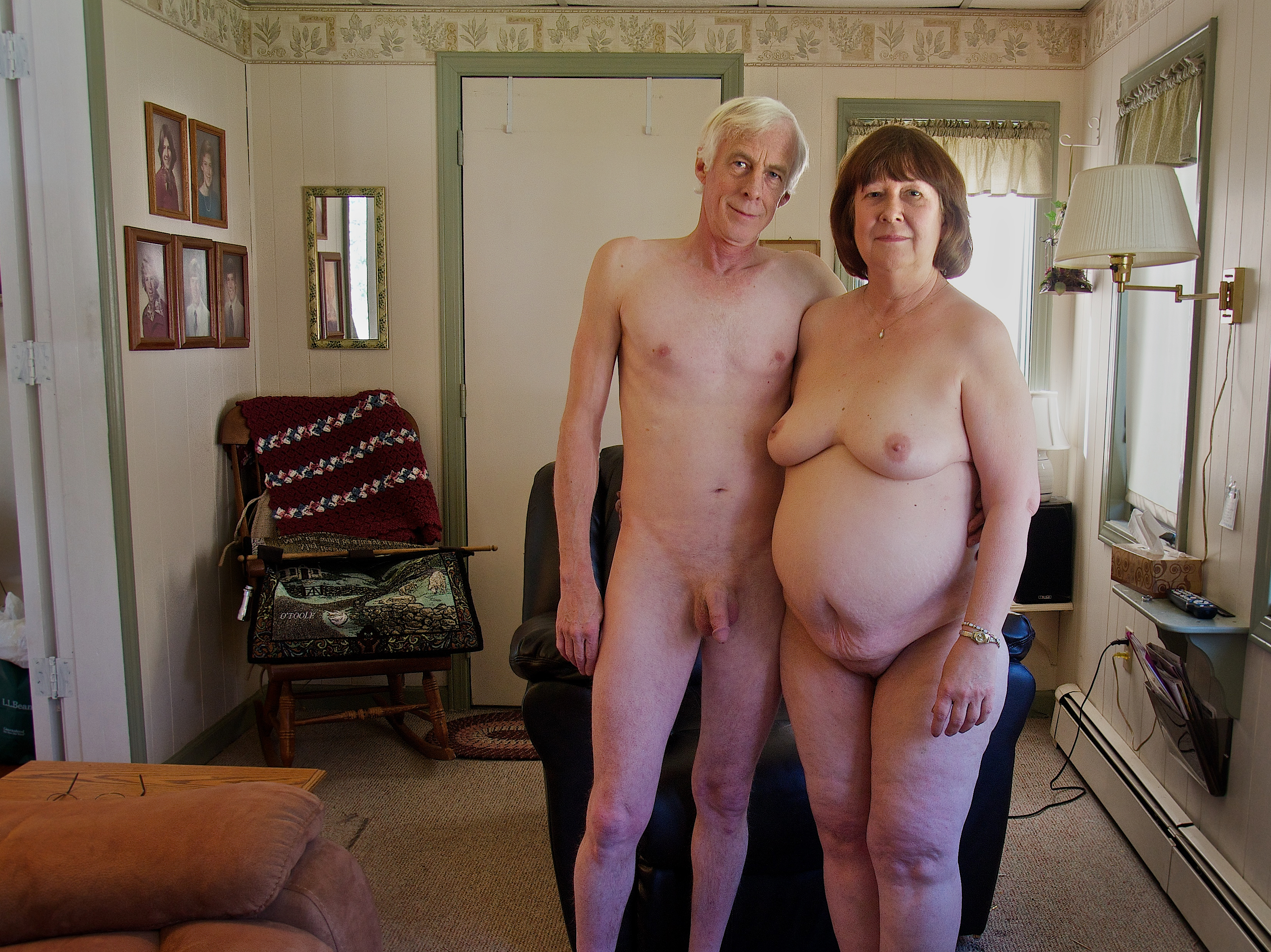 Nude older couple in their family room