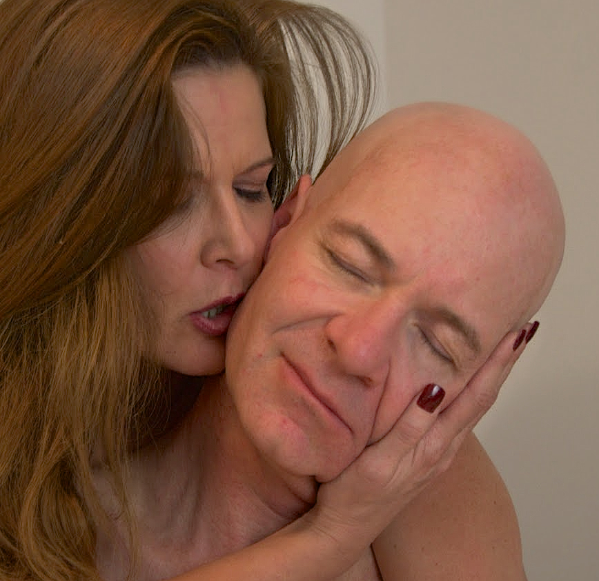 Bald man being kissed