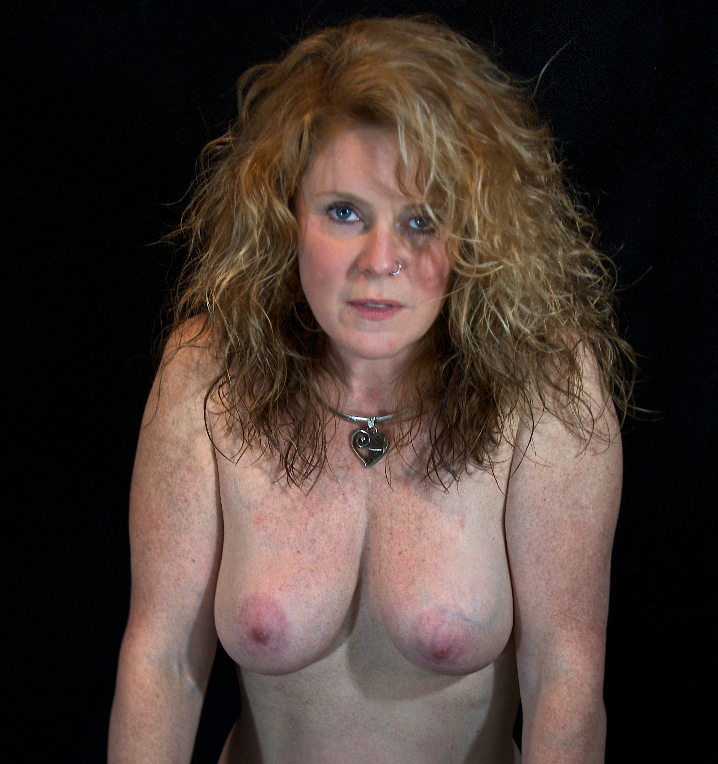 Bare-breasted woman with blue eyes and freckles